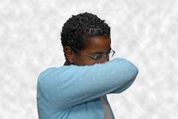 Woman sneezing into sleeve